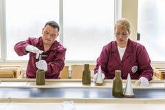 Lavoratori ad una catena di montaggio nella fabbrica della munizione Fotografia Stock