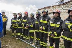 Lavoratori addetti al salvataggio al funerale delle vittime di terremoto fotografia stock