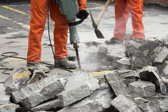 Lavoratori al cantiere che demoliscono asfalto fotografia stock