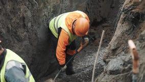Lavoratori in caschi arancio che remano macadam con le pale in fossa, rallentatore archivi video