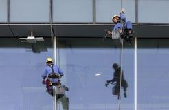 Lavoratori che appendono giù buiding per lavare le finestre Immagini Stock