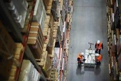 Lavoratori che contano nuova spedizione in magazzino immagini stock