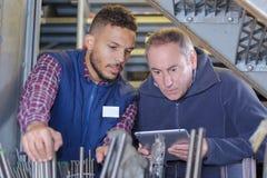 Lavoratori che controllano i tubi del metallo in magazzino Fotografie Stock