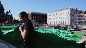 Lavoratori che costruiscono via per l'evento di estate sulla via Gli uomini tengono la tenda enorme verde archivi video
