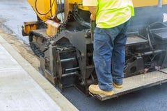 Lavoratori che fanno asfalto con le pale alla costruzione di strade immagine stock libera da diritti