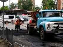 Lavoratori che fanno asfalto con le pale alla costruzione di strade Concep fotografia stock