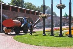 Lavoratori che innaffiano i fiori con un tubo flessibile dentro il Novgorod kremlin a Nizhny Novgorod immagine stock libera da diritti