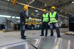 Lavoratori che lavorano con le billette di alluminio Immagine Stock