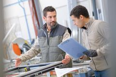 Lavoratori che montano le porte e le finestre del PVC alla fabbrica immagini stock