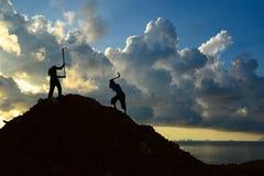 Lavoratori che per mezzo della zappa per scavare mucchio di suolo Immagini Stock