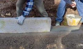 Lavoratori che pongono i bordi concreti Fotografie Stock Libere da Diritti