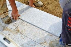 Lavoratori che pongono il lastricatore del blocchetto del granito sul posto Fotografie Stock