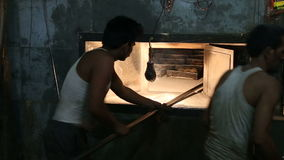 Lavoratori che prendono prodotti dal forno video d archivio