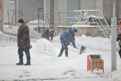 Lavoratori che puliscono il marciapiede nella bufera di neve pesante fotografia stock libera da diritti