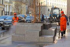 Lavoratori che puliscono via con il tubo flessibile dell'acqua a Mosca fotografie stock libere da diritti