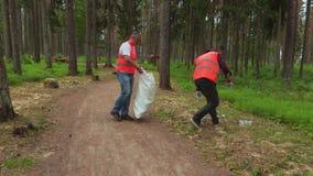 Lavoratori che raccolgono le bottiglie di plastica sul percorso nel parco