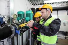 Lavoratori che riparano i tubi Immagini Stock