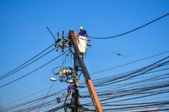 Lavoratori che riparano lavoro sul palo di potere elettrico della posta Fotografie Stock