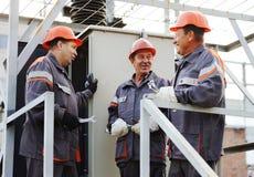 Lavoratori che riparano trasformatore elettrico immagini stock