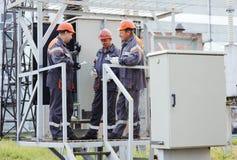 Lavoratori che riparano un trasformatore alla centrale elettrica immagini stock libere da diritti