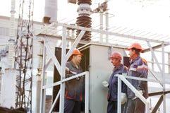 Lavoratori che riparano un trasformatore alla centrale elettrica fotografia stock