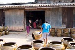 Lavoratori che rotolano i lotti dei vasi e dei vasi da fiori di progettazione del drago dalla stufa Fotografie Stock Libere da Diritti