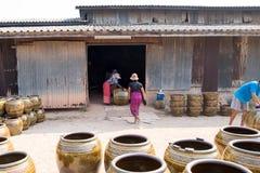 Lavoratori che rotolano i lotti dei vasi e dei vasi da fiori di progettazione del drago dalla stufa Fotografia Stock