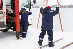 Lavoratori che scaricano i blocchi di ghiaccio da un'automobile fotografia stock