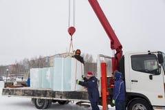 Lavoratori che scaricano i blocchi di ghiaccio da un'automobile fotografia stock libera da diritti