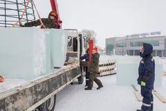 Lavoratori che scaricano i blocchi di ghiaccio da un'automobile fotografie stock