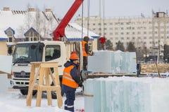 Lavoratori che scaricano i blocchi di ghiaccio da un'automobile immagini stock