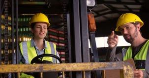 Lavoratori che si siedono in carrello elevatore e che parlano l'un l'altro nel magazzino stock footage