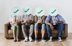 Lavoratori che si siedono e che tengono le icone del segno di spunta Immagine Stock Libera da Diritti