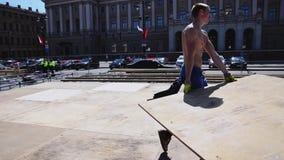 Lavoratori che sviluppano fase per l'evento di estate sulla via Gli uomini portano i bordi di legno stock footage