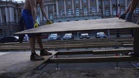 Lavoratori che sviluppano la fase della via per l'evento di estate Gli uomini hanno messo i bordi di legno sugli ostacoli video d archivio