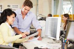 Lavoratori che utilizzano la compressa di Digital nell'ufficio creativo occupato immagini stock libere da diritti