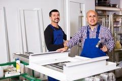 Lavoratori con le finestre e le porte del PVC Fotografia Stock