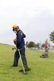 Lavoratori degli architetti di giardini che avviano il regolatore del gas e la falciatrice da giardino Fotografia Stock Libera da Diritti