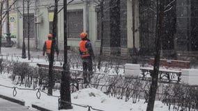 Lavoratori degli uomini che indossano il supporto del casco e dell'uniforme esterno in via il giorno di nevicata archivi video