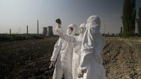 Lavoratori dei biologi in abbigliamento del hazmat che esamina pezzo contaminato di terra del suolo da un campo agricolo in della video d archivio