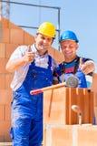 Lavoratori del cantiere che costruiscono le pareti sulla casa Immagini Stock Libere da Diritti