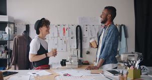 Lavoratori del tipo e della ragazza dello studio di modo che parlano tenendo caffè per andare rilassarsi video d archivio