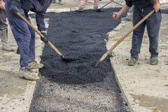 Lavoratori dell'asfalto con le pale che rattoppano asfalto fotografie stock libere da diritti