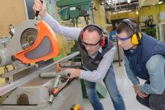 Lavoratori dell'industria che per mezzo della macchina della taglierina del metallo immagini stock libere da diritti