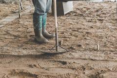 Lavoratori dell'uomo che spargono miscela di calcestruzzo di recente versata Immagini Stock Libere da Diritti