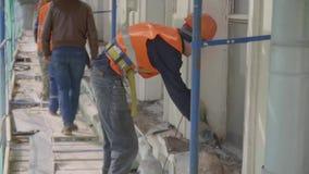 Lavoratori di alcuni maschi nella posa di ponteggi uniforme coperta di rete verde stock footage