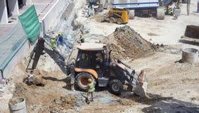 Lavoratori di Construciton su un sito con l'escavatore fotografia stock libera da diritti