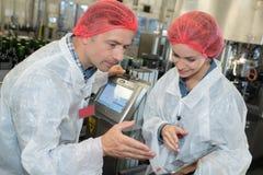 Lavoratori di metallurgia in officina facendo uso della compressa digitale fotografia stock libera da diritti