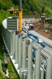 Lavoratori durante l'installazione delle barriere di rumore sulla strada principale Immagine Stock