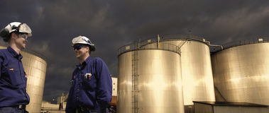 Lavoratori e carri armati dell'olio al tramonto Fotografia Stock